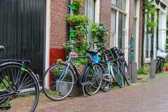 Parkerade cyklar nära tegelstenhuset på den smala gatan Royaltyfri Bild