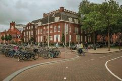 Parkerade cyklar och cyklist som gör kurvan i gata med molnig himmel på Amsterdam Royaltyfri Fotografi