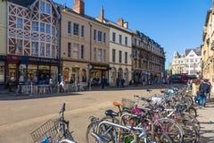 Parkerade cyklar och folk som ut Uni hänger på en gata i Oxford Royaltyfria Bilder