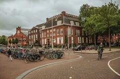 Parkerade cyklar och kvinna som trampar i gata med molnig himmel i Amsterdam Arkivfoton