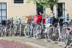 Parkerade cyklar på en räcke i historiskt kanalbälte av Amsterdam, Arkivbild
