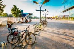 Parkerade cyklar på trottoaren nära det Sanoma huset i HELSINGFORS, FINLA Royaltyfri Foto