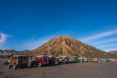 Parkerade jeepar 4x4 på en öken med monteringsbatok på bakgrunden Arkivfoto