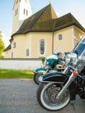 Parkerade motorcyklar framme av en kyrka arkivbilder