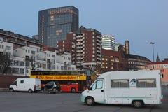 Parkerade skåpbilar och en sightbuss i cityscapen Arkivbild