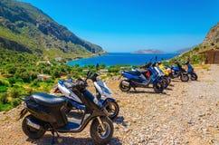 Parkerade sparkcyklar och havsfjärd med stranden, Grekland Arkivbild