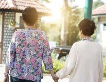 Parkerar asiatiska äldre kvinnor för den bakre sikten som går på utomhus- royaltyfria bilder