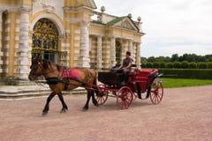 Parkerar av Moskva Nobelt gods Kuskovo Hästdragna vagnsritter bredvid grottapaviljongen royaltyfri bild