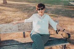 Parkerar den älskvärda latinamerikanska mitt åldrades kvinnan i att sitta på en bänk på solnedgången fotografering för bildbyråer