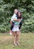 Parkerar den åriga Amerasian flickan för tretton med hennes åriga Amerasian syster för tio som rider ridtur på axlarna i Washinto fotografering för bildbyråer