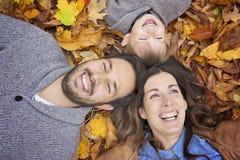 Parkerar den avslappnande det fria för lycklig familj i höst Royaltyfri Bild