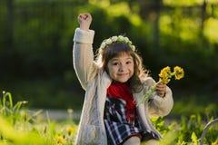 Parkerar den bärande kransen för den gulliga unga flickan av maskrosor och att le, medan sitta på gräs, in royaltyfria bilder