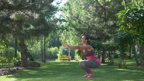 Parkerar den färdiga kvinnan för aktiv som gör squats i sommar stock video