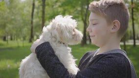 Parkerar den förtjusande gulliga unga pojken för ståenden som rymmer en vit fluffig hund i den härliga gräsplanen arkivfilmer