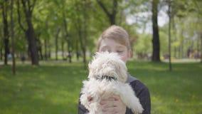 Parkerar den förtjusande unga pojken för ståenden som rymmer en vit fluffig hund i den härliga gräsplanen arkivfilmer