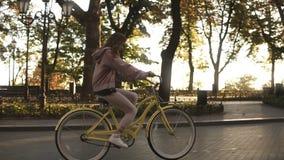 Parkerar den gula färgade cykeln för den nätta liten flickaridningen på gatan i sommarstad Träd och sunshines på bakgrunden stock video