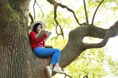 Parkerar den härliga kvinnaflickan för den lyckliga gulliga asiatiska kinesiska naturen i en vår tycker om den lästa boken för fr royaltyfri bild