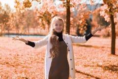 Parkerar den härliga ståenden för hösten av en ung flicka i med lövverk tonåringleenden och händer upp arkivbilder