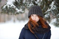 Parkerar den härliga vinterståenden för closeupen av den unga förtjusande rödhårig mankvinnan i gulliga stack den snöig hattvinte royaltyfria bilder