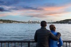 Parkerar den hållande ögonen på solnedgången för par på gasarbeten i Seattle royaltyfri fotografi