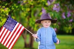 Parkerar den hållande amerikanska flaggan för den gulliga litet barnpojken i härligt Arkivbild