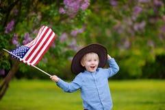 Parkerar den hållande amerikanska flaggan för den gulliga litet barnpojken i härligt Royaltyfri Fotografi