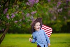 Parkerar den hållande amerikanska flaggan för den gulliga litet barnpojken i härligt Arkivfoton
