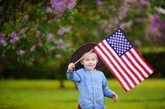 Parkerar den hållande amerikanska flaggan för den gulliga litet barnpojken i härligt Arkivfoto