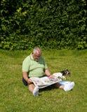 Parkerar den läs- tidningen för den äldre mannen in Arkivfoto