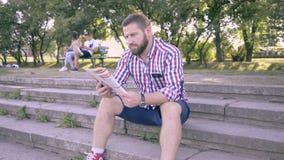Parkerar den läs- tidskriften för den unga mannen, sammanträde på trappa in stock video