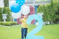 Parkerar den lyckliga asiatiska ungeställningen för closeupen med ballongen i hans hand på gräsgolv in texturerad bakgrund i conc royaltyfri foto