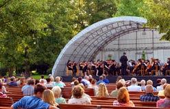 Parkerar den lyssnande klassiska musikkonserten för folk in trädgården Arkivbild