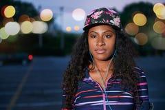 Parkerar den millennial flickan för afrikanska amerikanen som ser bort det fria i ett stads-, sen afton med den iklädda moderikti Fotografering för Bildbyråer