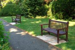 Parkerar den på engelska sommarträdgården för den stilfulla bänken arkivfoton