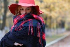 Parkerar den röda hatten för den allvarliga kvinnan i höst Royaltyfri Fotografi