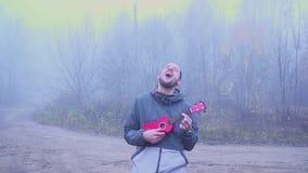 Parkerar den stiliga mannen för ståenden som spelar den bas- ukulelet i, musikbegreppet lager videofilmer