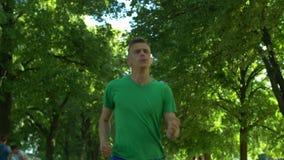 Parkerar den stiliga mannen för den sunda passformen som in joggar arkivfilmer