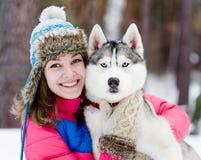 Parkerar den tonåriga flickan för closeupen som omfamnar den gulliga hunden i vinter Arkivfoton