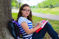 Parkerar den tonåriga flickan för den klyftiga studenten med skolapåsen under trädet Arkivbild