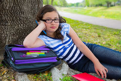 Parkerar den tonåriga flickan för den klyftiga studenten med skolapåsen under trädet Arkivbilder