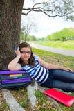 Parkerar den tonåriga flickan för den klyftiga studenten med skolapåsen under trädet Royaltyfri Bild