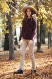 Parkerar den unga kvinnan för det lyckliga leendet som utomhus går i höst, i hemtrevlig tröja och hatt Varmt soligt väder Nedgång arkivfoton