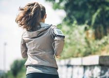 Parkerar den unga kvinnan för kondition som joggar i staden Arkivfoto
