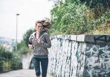 Parkerar den unga kvinnan för kondition som joggar i staden Royaltyfri Foto