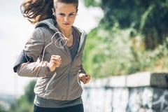 Parkerar den unga kvinnan för kondition som joggar i staden royaltyfri bild