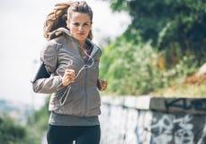 Parkerar den unga kvinnan för kondition som joggar i staden Royaltyfria Bilder