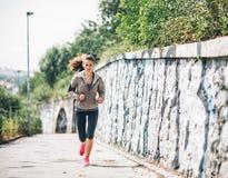 Parkerar den unga kvinnan för kondition som joggar i staden Royaltyfri Fotografi