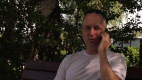 Parkerar den vuxna mannen för ståenden som talar till mobiltelefonen på bänk i sommarstad stock video