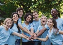 Parkerar det utomhus- mötet för unga lyckliga volontärer på royaltyfri fotografi