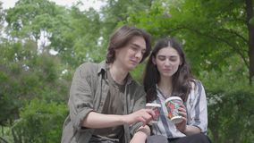 Parkerar förtjusande unga gulliga par för stående i tillfällig kläder som spenderar tid tillsammans i och att ha datumet Studente lager videofilmer